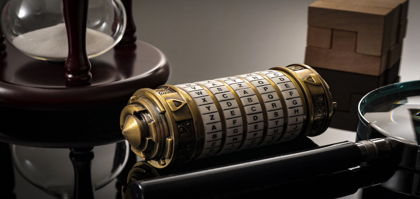 old ciphertext mechanism on a desk with an hourglass