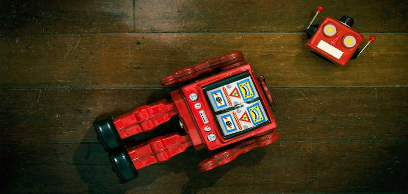 picture of a red retro robot laying on the floor, head detached