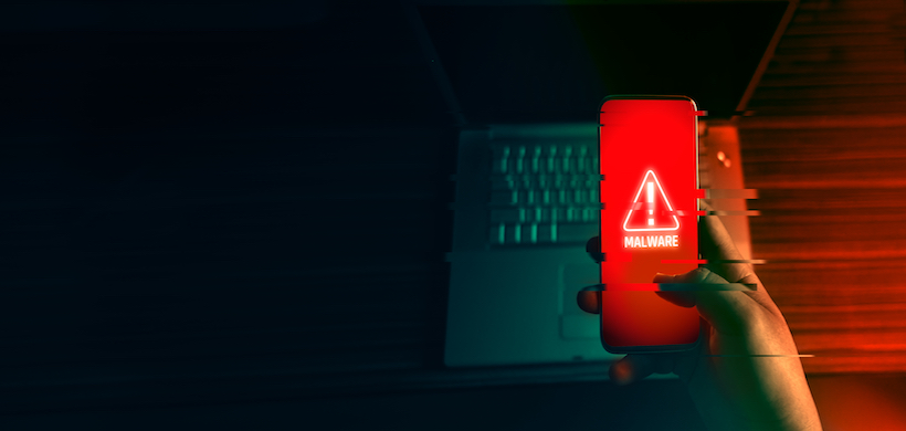"image of a person holding a cell phone with the word ""malware"" and a warning triangle on the screen"
