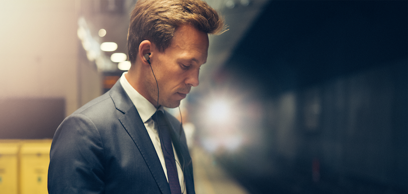 image of businessman with headphones, in a subway at night