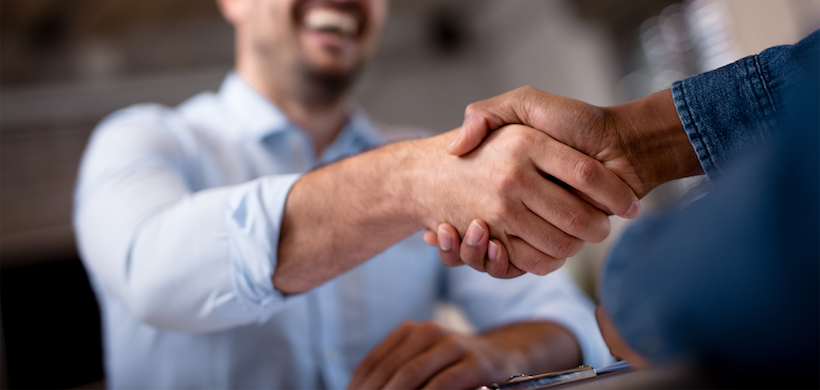 two men in business attire shaking hands