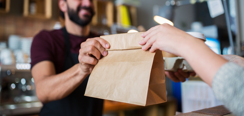 image of a bearded man behind a counter handing a brown paper bag of food to a patron