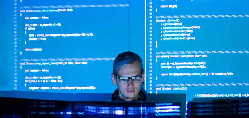 picture of a man coding on several monitors with two giant screens projected behind him, displaying code
