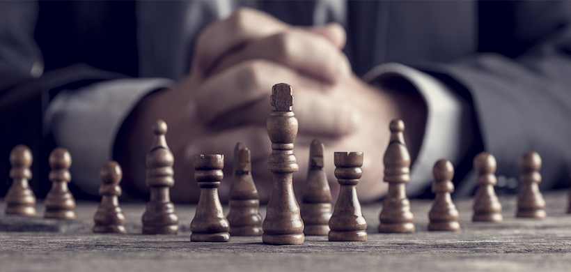 Shot of man's hands folded behind a wooden chess set. Man is wearing business attire.