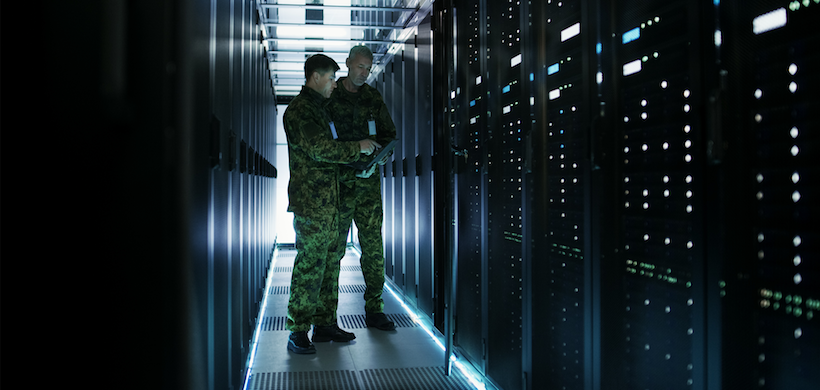 two men in fatigues in a large hallway full of servers
