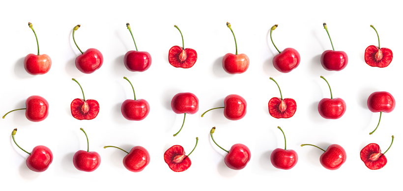 three rows of cherries lined up, some cut in half, on a white background