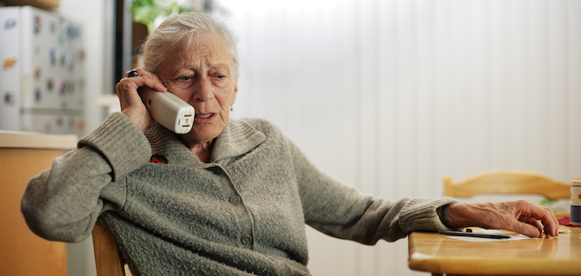 an elderly woman sitting at the kitchen, talking on the phone with a worried look on her face