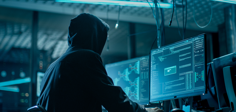 image of a hooded hacker sitting in a dark room in front of several computer monitors
