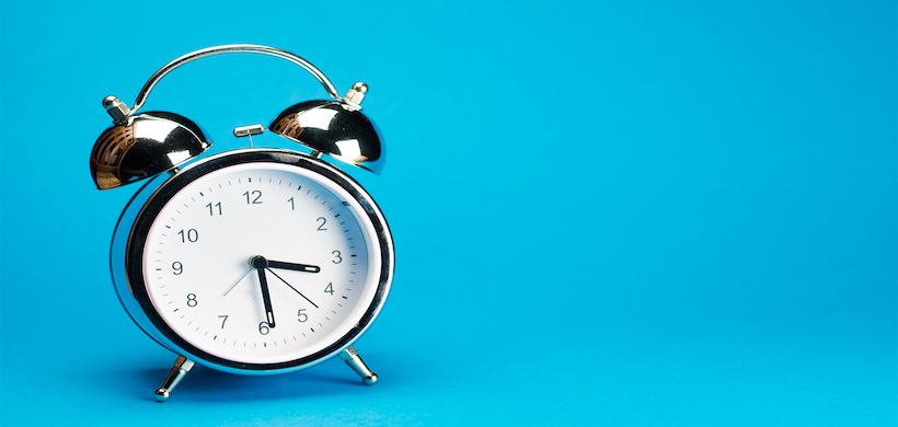 image of a silver alarm clock at 3:29 against a blue background