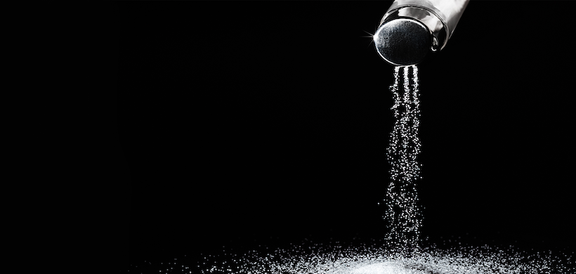 image of a salt shaker pouring salt into a pile, against a black background
