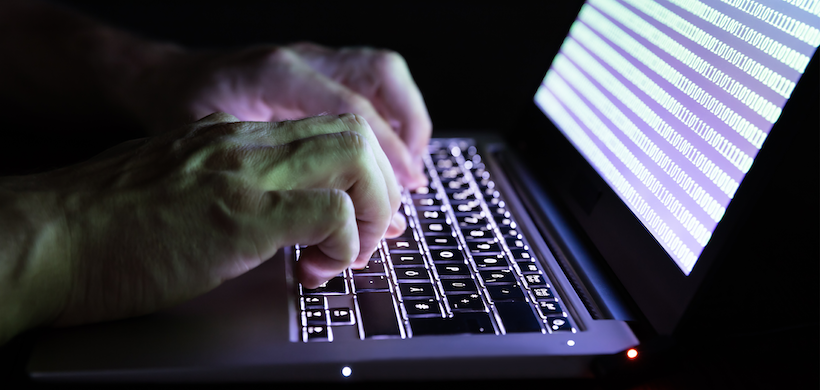 image of hands typing on a keyboard in the dark