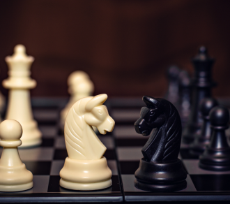 two chess knights pieces facing off on a full board