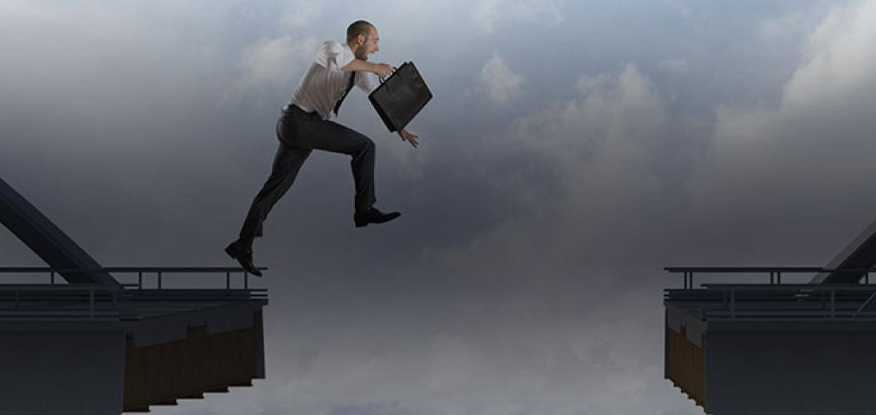 businessman jumping across a wide gap in a high bridge, briefcase in his hand