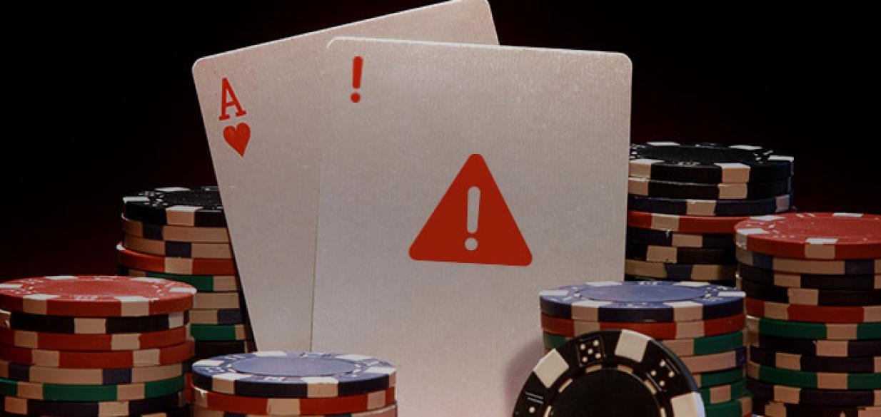 playing cards and chips in a gambling setting, one card has a digital electronic warning triangle on it