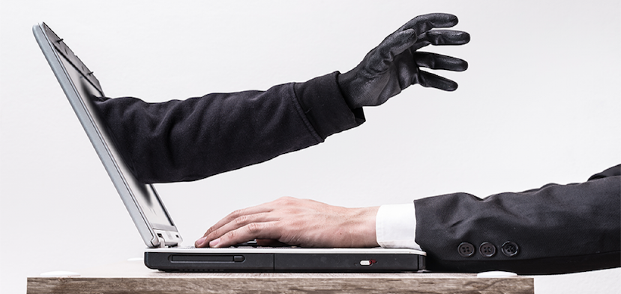image of a thief reaching out from a laptop screen to grab the arm of a businessman on the other side of the screen