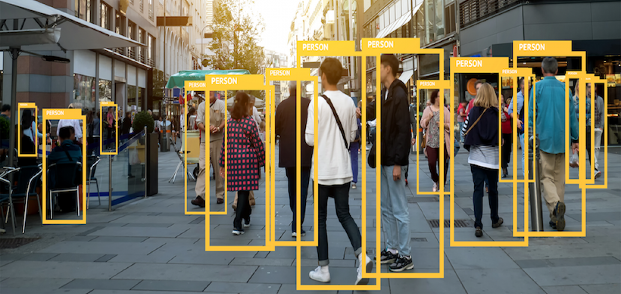 picture of a group of people in an outdoor plaza with yellow rectangles around them, identifying them as if by AI