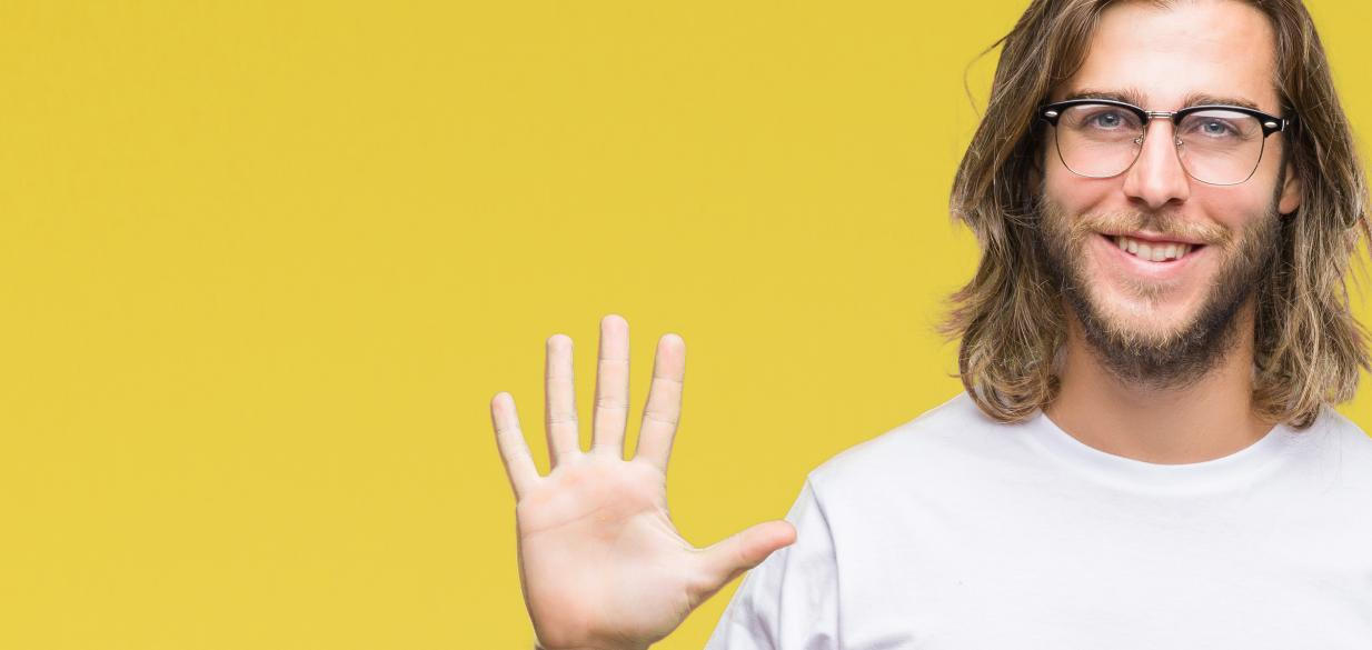 young man with long hair and glasses holding up 5 fingers against a yellow background