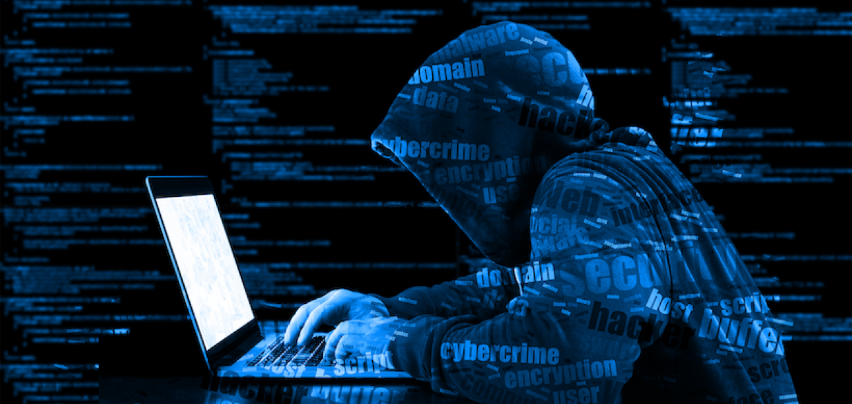 cyber attacker typing on a laptop in a dark room