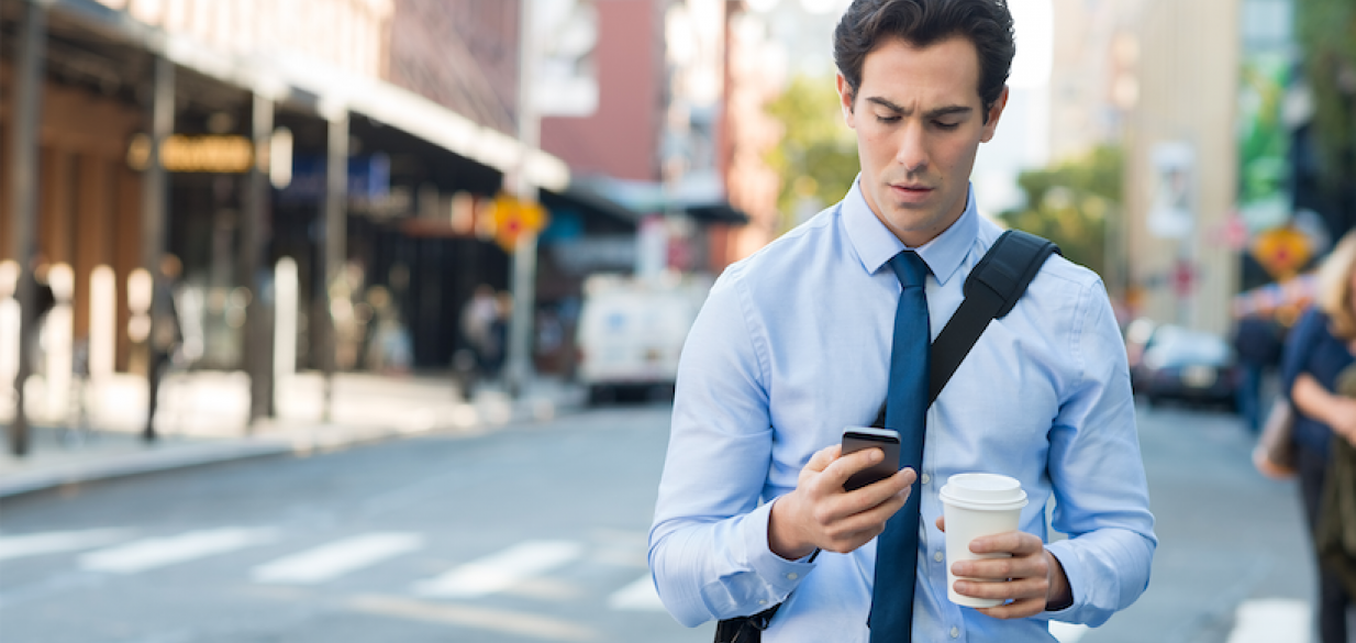 young professional man staring down at his phone in dismay while standing on a city street holding a coffee in one hand