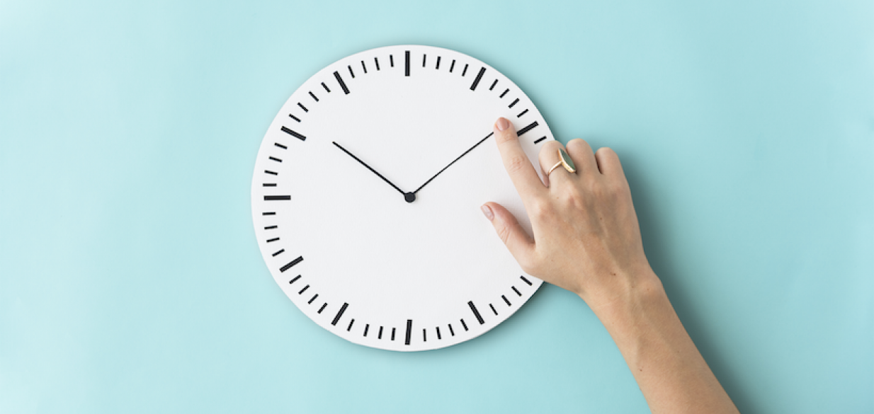 image of a hand touching the minute hand of a white modern clock set at 10:10, against a light blue wall