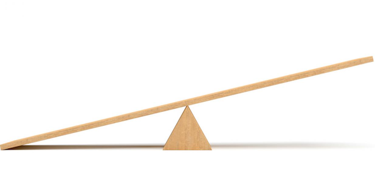 image of a wooden teeter totter against a white background, with one end up and the other end on the ground